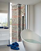 Moderne Badewanne mit Blick auf die Backsteinfassade