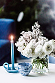 Blue candle, small bowl and white bouquet on coffee table