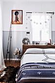 Doppelbett vor Fenster, gerahmtes Foto und Angelrute im Schlafzimmer, Klappstuhl mit verpackten Geschenken