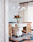 Designer table with rattan armchairs, bouquet of flowers and white chandelier