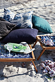 Cushions and folding trays on sandy beach