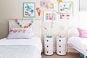 Children's room with two beds, bedside tables and children's drawings on the wall