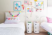 Kinderzimmer mit zwei Betten, Nachttischen und Kinderzeichnungen an der Wand
