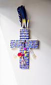 Blue patterned cross decorated with pompom and feathers