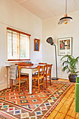 Wooden table with chess board and chairs in front of window, floor lamp and houseplant in the background