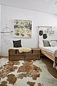 Rattentruhen mit Schaffell neben Bett und Tierfellteppich im Schlafzimmer