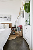 Bed and built-in chest of drawers in the bedroom with white walls