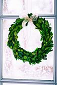 Wreath of box leaves in window