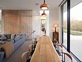 Langer Holztisch vor der Fensterfront zur Terrasse im offenen Wohnraum