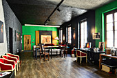 Red chairs, dining table and desk in renovated loft apartment with black and green walls