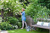 Woman smelling white roses in idyllic summer garden