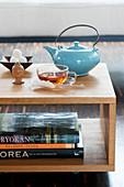 Teetasse, Teekanne und Buddhakopf auf Couchtisch