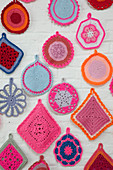 Many crocheted doilies on white brick wall