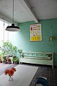 Holzbank und Pflanzen auf überdachter Terrasse mit grüner Wand