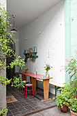 Holztisch mit Bank und Hocker auf Veranda mit weißer Ziegelwand