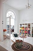 Beistelltische und Klassiker-Schaukelstuhl auf gehäkeltem Teppich vor Bücherregal