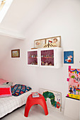 Brightly coloured accessories in child's attic bedroom