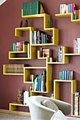 Gelbes Designer-Bücherregal an dunkelroter Wand