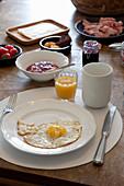 Gedeckter Frühstückstisch mit Spiegelei und Orangensaft