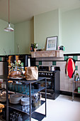View into kitchen with crockery on open shelves and mint-green walls