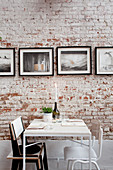 Table for two in front of photos on brick wall