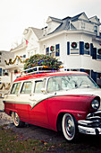 Classic car with decorated Christmas tree on roof rack
