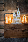 House-shaped Christmas decoration and fairy lights in glass vases