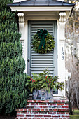 Front door decorated with Christmas wreath and Christmas arrangement on steps
