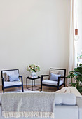 View of armchairs and side table seen across sofa