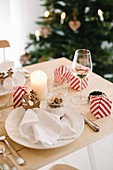 Christmas place setting with gingerbread mousse in glass bowl and favours in red-and-white striped boxes