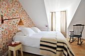 Gästezimmer mit Doppelbett und gemusterter Tapete im Dachgeschoss