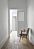 Schlichter, weißer Flur mit Holzdielenboden und Polsterstuhl