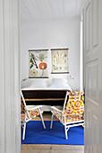 Blick ins Schlafzimmer mit bunten Stühlen und Doppelbett