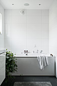 Bathtub in white bathroom with black floor