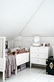 Vintage furnishings in child's white attic bedroom