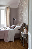 Feminine bedroom in pink and grey with herringbone parquet floor and stucco ceiling