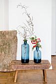 Zwei blaue Vasen mit Zweigen auf einem alten Schemel