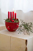 Advent arrangement of four red candles in red mixing bowl