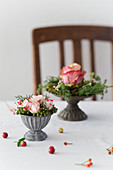 Small flower arrangements in grey metal bowls on table