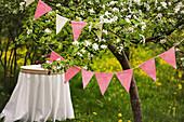 Blühender Kirschbaum mit Wimpelkett, im Hintergrund runder Tisch