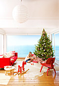Blonde woman puts gifts under Christmas tree, rocking horse in foreground in living room with sea view
