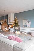 Hängesessel und Weihnachtsbaum am Kamin im Wohnzimmer mit blauer Wand