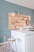 weiße Kücheninsel mit Barhockern, DIY-Holzboard für Dekoration an hellblauer Wand