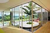 Cubic glass light well containing garden in modern, architect-designed house