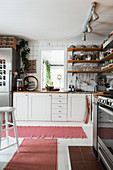 Shelves on walls above base units in bright kitchen with pink rugs