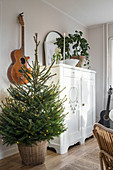 Christmas tree, guitar on wall and white cupboard in living room