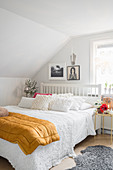 Double bed in white attic bedroom