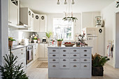 Island counter and Christmas decorations in bright fitted kitchen
