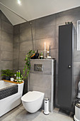 Bathtub and toilet in bathroom with grey wall tiles