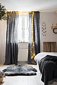 Fairy lights on grey curtains in bedroom